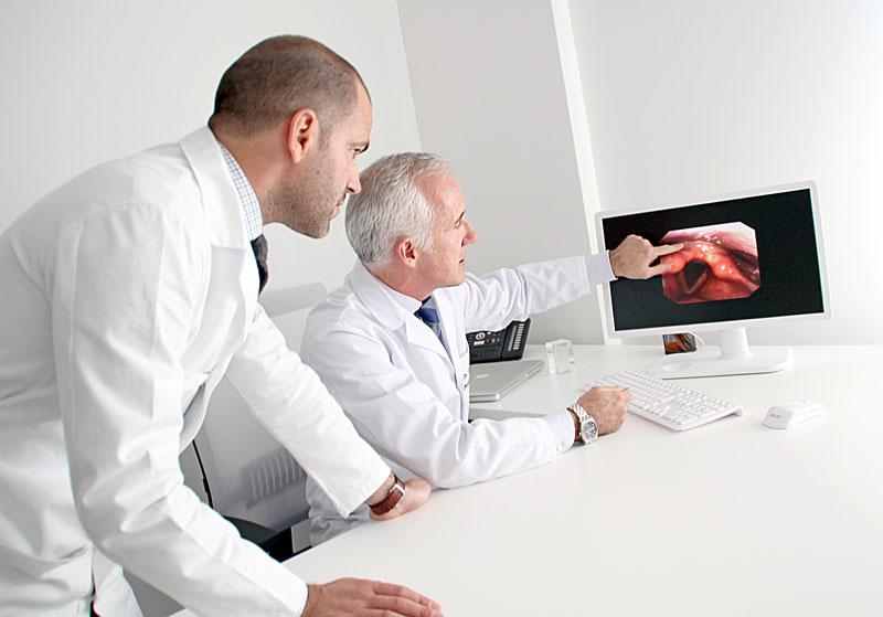 FOTO de los Dres Carlos Saga y Xabier Altuna mostrando uno de los estudios de la voz realizado en Policlínica.