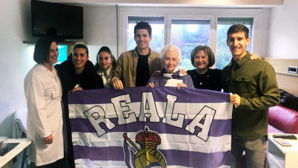 Los jugadores de la Real Sociedad posando con Maite, acompañada de su hija y la Dra. Sonia Roussel, directora médico-asistencial del centro